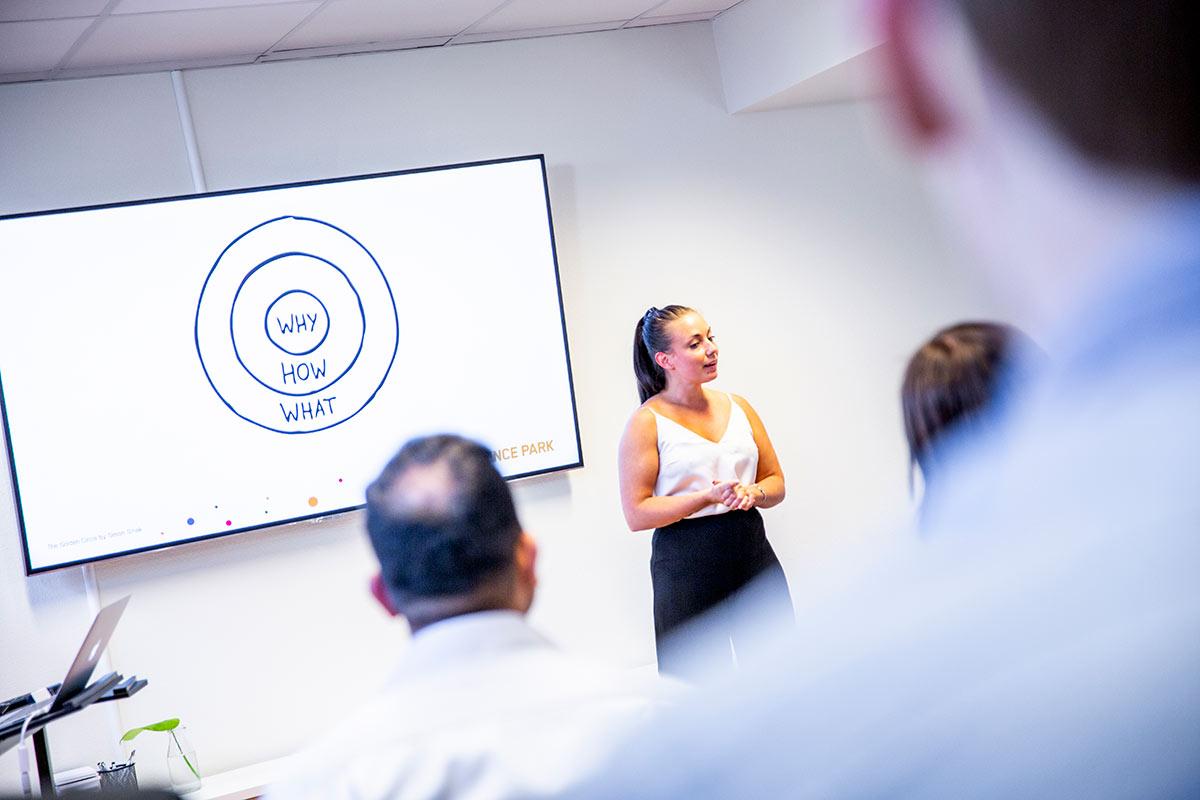 Entreprenör står framför en publik och pitchar. Hon har en skärm bakom sig.