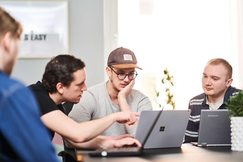 teamet bakom startupen employchain tittar på en laptop tillsammans