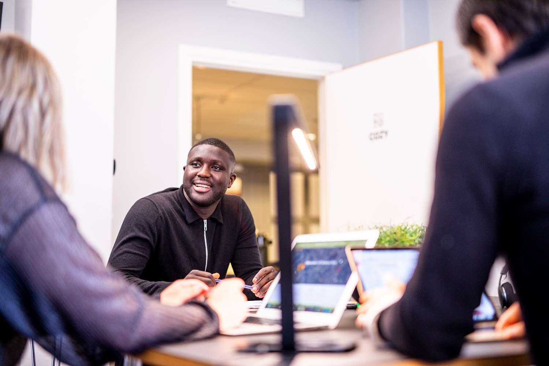 Fokus på en glad man som sitter i ett mötesrum och pratar med sina kollegor