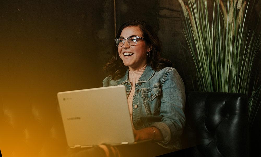 Kvinna sitter i en soffa med en laptop i knät. Hon skrattar och tittar åt sidan.