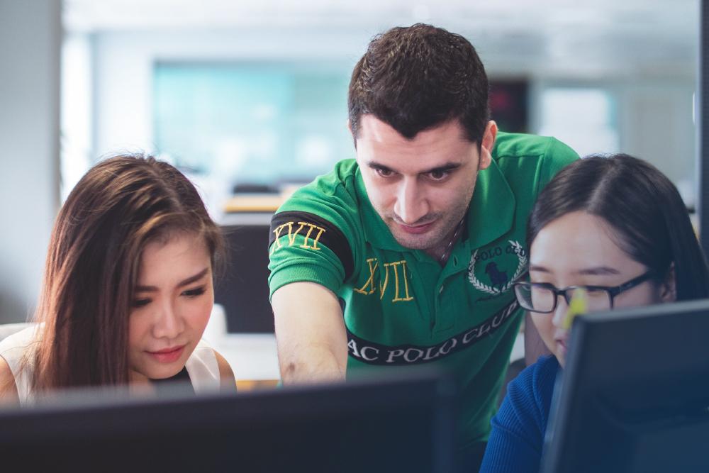 En man och två kvinnor tittar in i en dator.