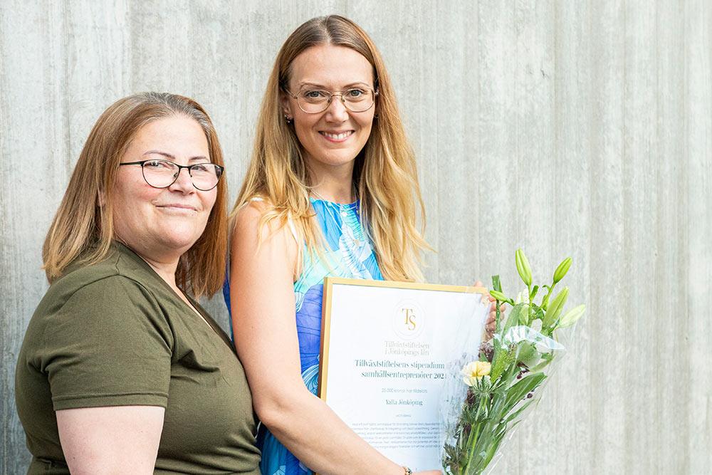 Nabila Youkhanna och Johanna Basth står glada med diplom och blommor framför betongvägg
