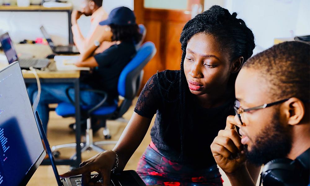 Två personer jobbar tillsammans och kollar in i en dator.