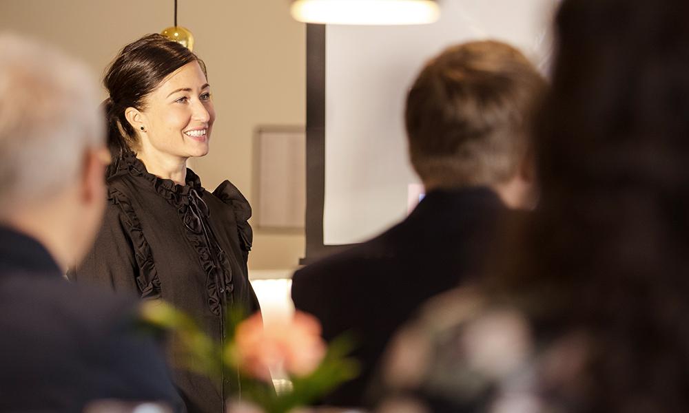 Kvinna står upp och håller i en presentation framför en grupp människor.
