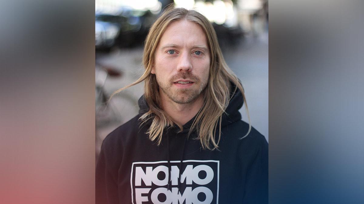 Nicklas Hermansson i en svart luvtröja med texten NOMOFOMO