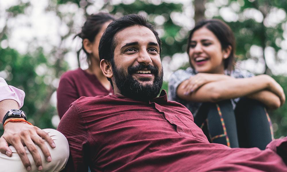 En man ligger ner utomhus. Har på sig röd tröja och ler. Två kvinnor syns skrattandes i bakgrunden.