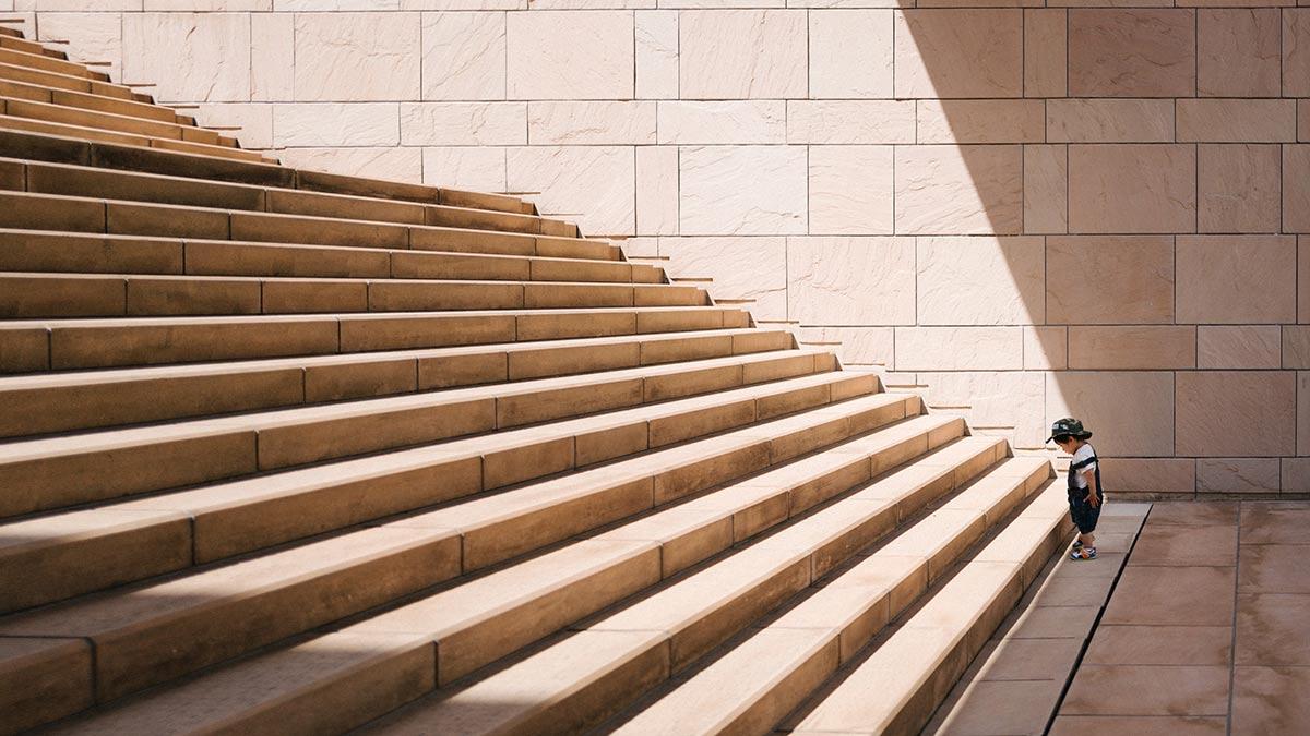 Litet barn står längst ned vid en stor trappa som lyses upp av solen