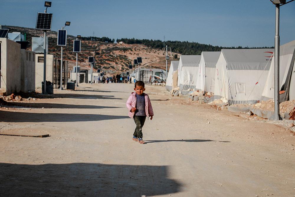 litet barn på sandig väg i flyktingläger